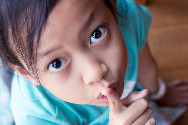 Garota de criança asiática secreto retrato closeup colocando dedo manter gesto quieto Foto Premium