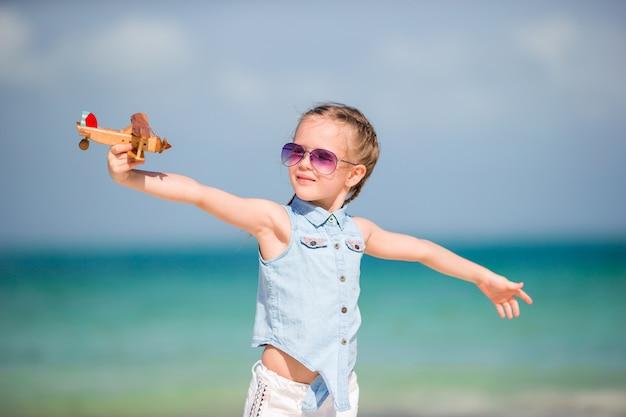 Garota de criança feliz brincando com o avião de brinquedo na praia. kid sonho de se tornar um piloto Foto Premium