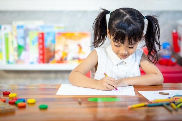 Garota de criança pré-escolar, desenho e colorir | Foto Premium