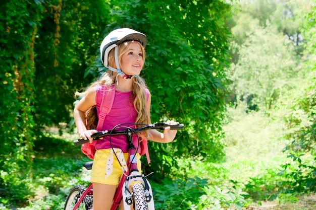 Garota de crianças andando de bicicleta ao ar livre na floresta sorrindo Foto Premium