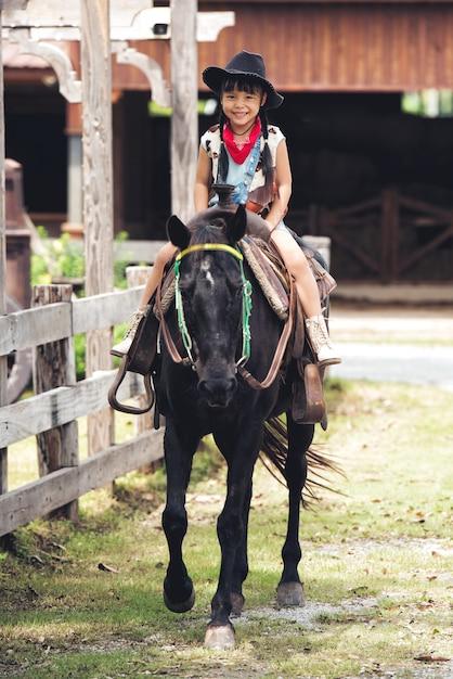 Garota de crianças ásia pequena sorriso feliz com chapéu está montando um cavalo preto Foto Premium