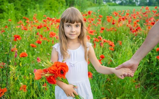Garota de crianças em um campo com papoulas. Foto Premium