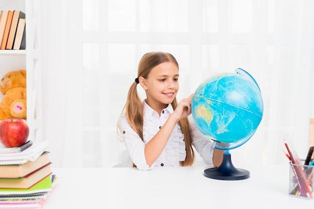 Garota de escola primária com globo Foto gratuita