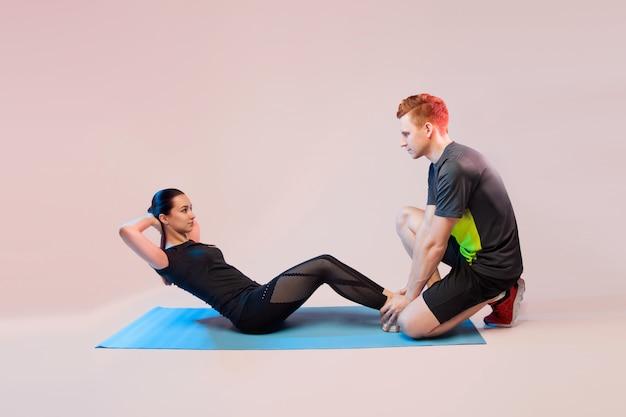 Garota de esportes e cara fazendo exercícios. ele ajuda a garota a agitar a imprensa. Foto Premium