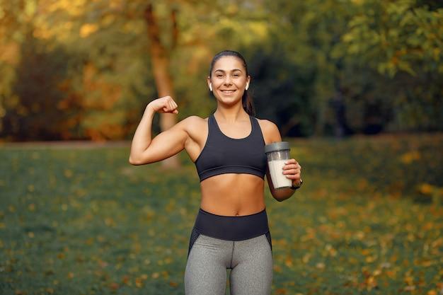 Garota de esportes em um treinamento top preto em um parque de outono Foto gratuita