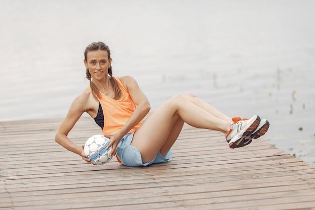 Garota de esportes na água. mulher em um parque de verão. senhora em um sportswear laranja. Foto gratuita