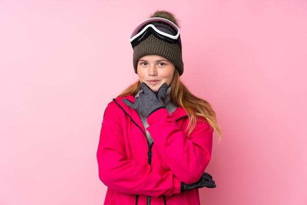 Garota de esquiador adolescente ucraniano com óculos de snowboard sobre riso rosa isolado Foto Premium