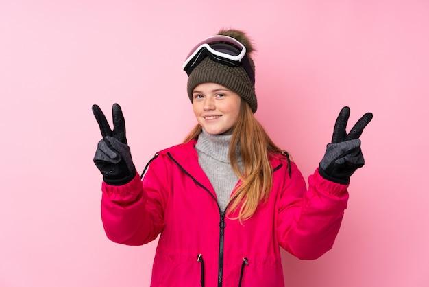 Garota de esquiador adolescente ucraniano com óculos de snowboard sobre rosa isolado sorrindo e mostrando sinal de vitória Foto Premium