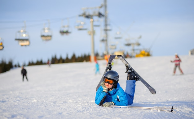 Garota de esquiador deitado na neve em um dia ensolarado contra teleférico na estância de esqui Foto Premium