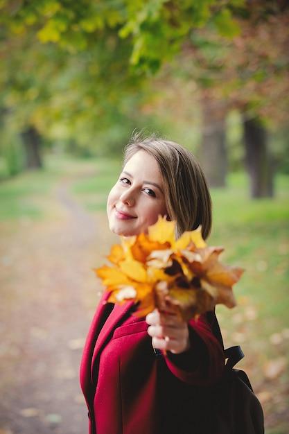 Garota de estilo jovem com folhas no beco do parque Foto Premium
