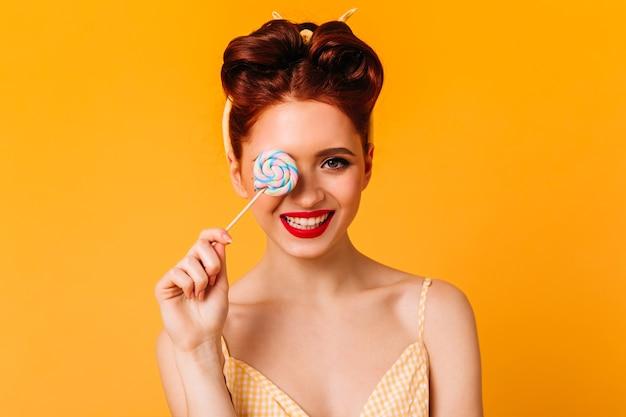 Garota de gengibre emocional segurando pirulito e sorrindo. vista frontal de uma mulher europeia com rebuçados. Foto gratuita