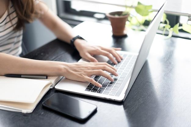 Garota de negócios asiáticos começar a trabalhar com o computador portátil no café Foto Premium