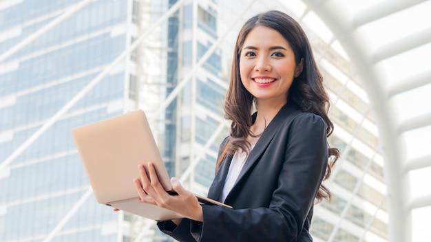 Garota de negócios com computador notebook e cidade de fundo. Foto Premium