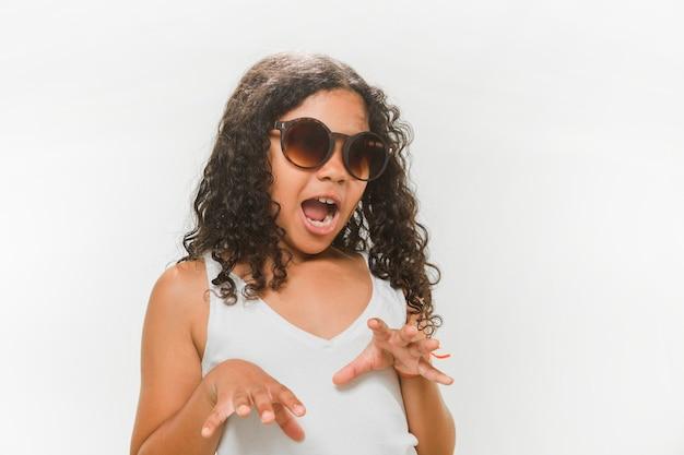 Garota de óculos de sol tentando assustar no fundo branco Foto gratuita