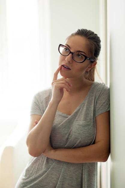 Garota de óculos pensando Foto gratuita
