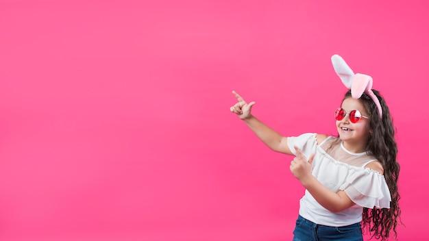 Garota de orelhas de coelho, apontando para fora Foto gratuita