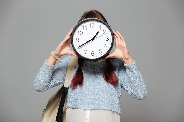 Garota de pé cobrindo o rosto com relógio Foto gratuita