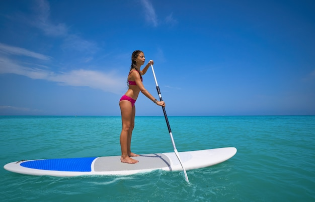 Garota de pé na prancha de surf paddle Foto Premium