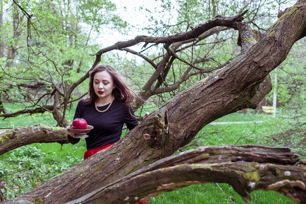 Garota de pé perto de um tronco de árvore Foto Premium