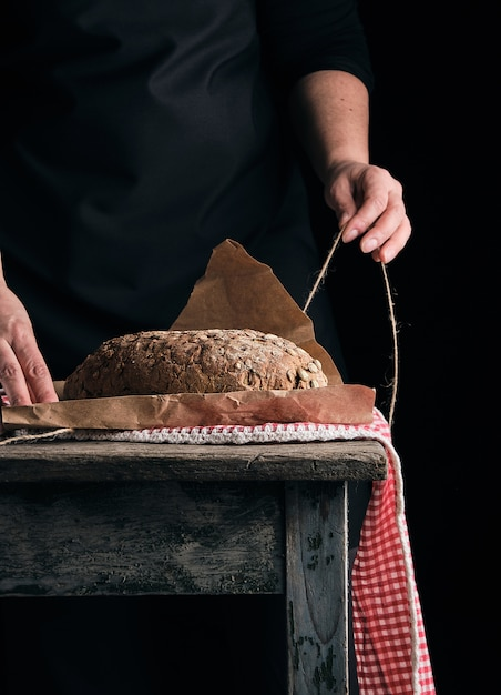 Garota de roupas pretas envolve um pão todo cozido em papel kraft marrom Foto Premium