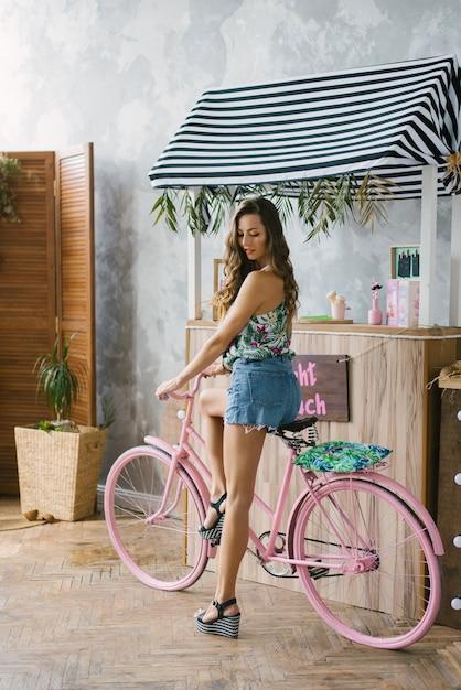 Garota de short jeans com pernas longas em uma bicicleta rosa perto do bar Foto Premium