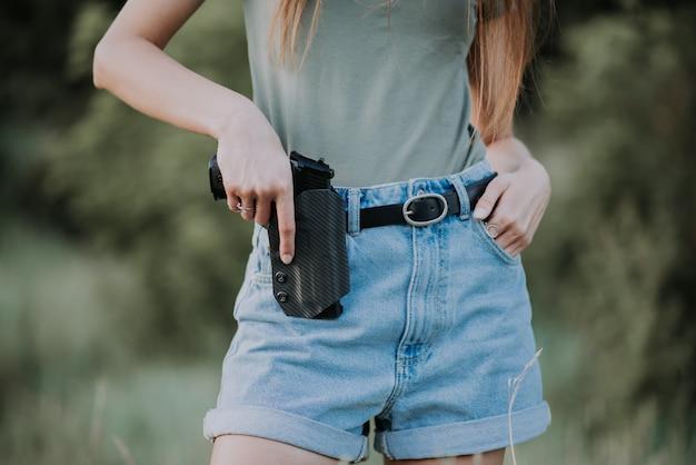 Garota de short jeans e com uma arma na mão, posando no campo. fechar-se Foto Premium