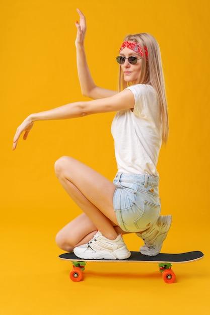 Garota de skateborder em shorts e camiseta, sentado a bordo, sobre fundo amarelo Foto Premium