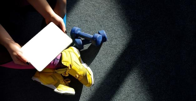 Garota de tênis amarelo segura um tablet com pesos para treinamento. conceito de aprendizagem online. Foto Premium