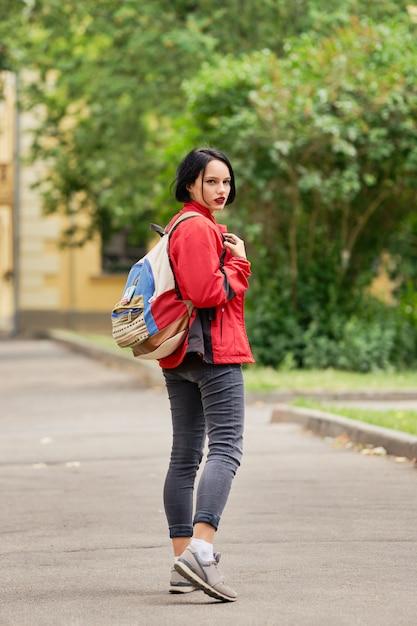 Garota de turista com mochila de lona, olhando para trás na rua Foto Premium