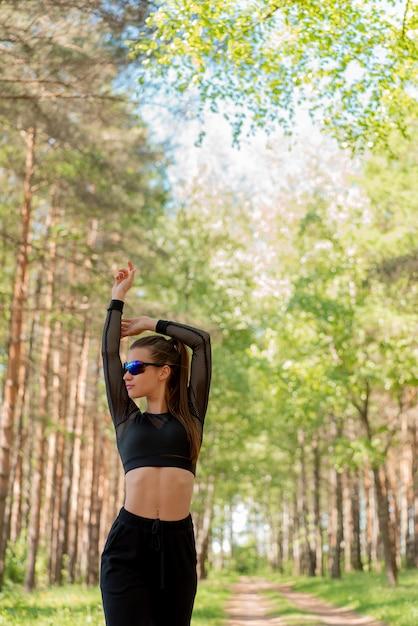 Garota de uniforme e óculos de sol fazendo esportes em um parque Foto Premium