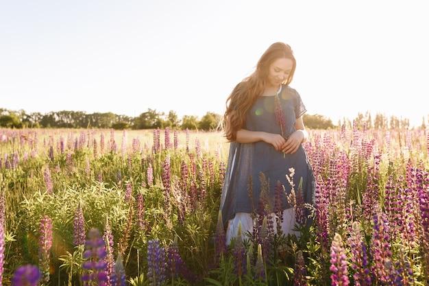 Garota de vestido azul andando no campo de flores. Foto gratuita