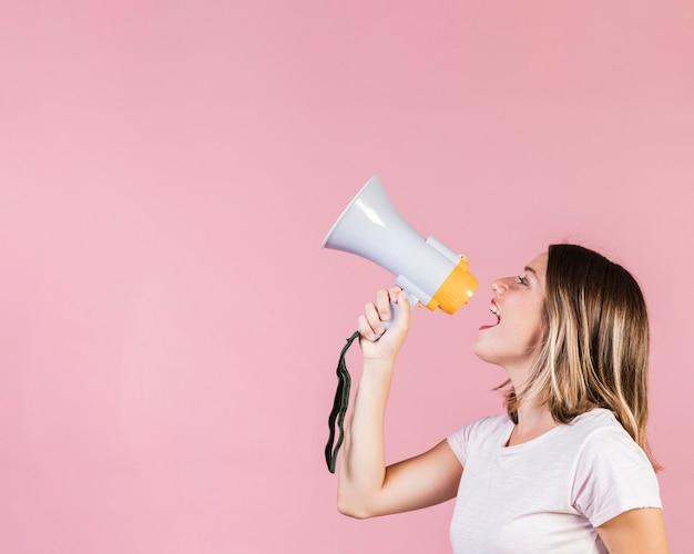 Garota de visão lateral falando em um megafone Foto Premium