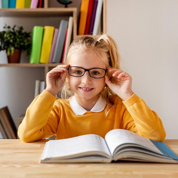 Garota de vista frontal com óculos de leitura Foto gratuita