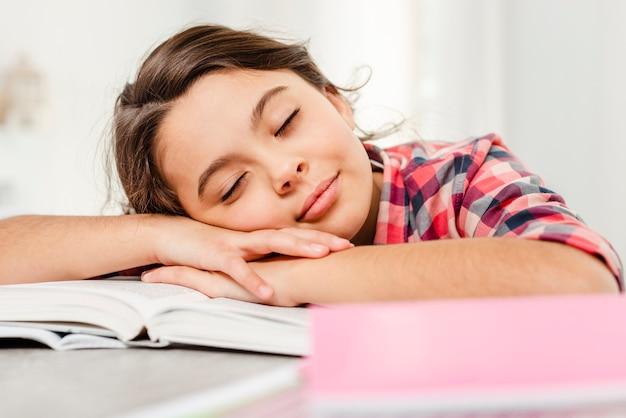 Garota de vista frontal dormindo no livro Foto gratuita