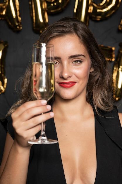 Garota de vista frontal, segurando uma taça de champanhe Foto gratuita