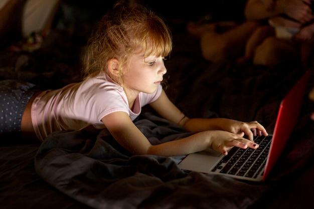 Garota de vista lateral na cama com o laptop Foto gratuita