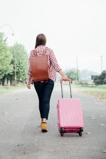 Garota de vista traseira com mochila e bagagem rosa Foto gratuita