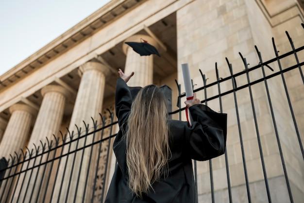 Garota de vista traseira jogando seu trencher Foto gratuita