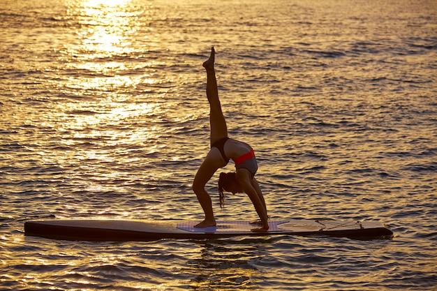 Garota de yoga sobre sup stand up surf board Foto Premium