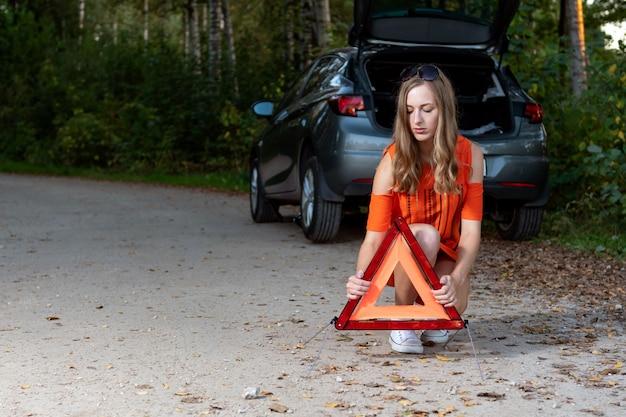 Garota define um triângulo na parte de trás do carro quebrado Foto Premium