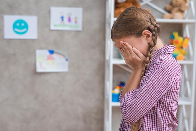 Garota deprimida, cobrindo o rosto com as duas mãos Foto gratuita