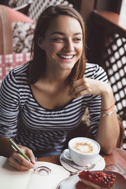 Garota desenhando uma xícara de café no caderno Foto gratuita