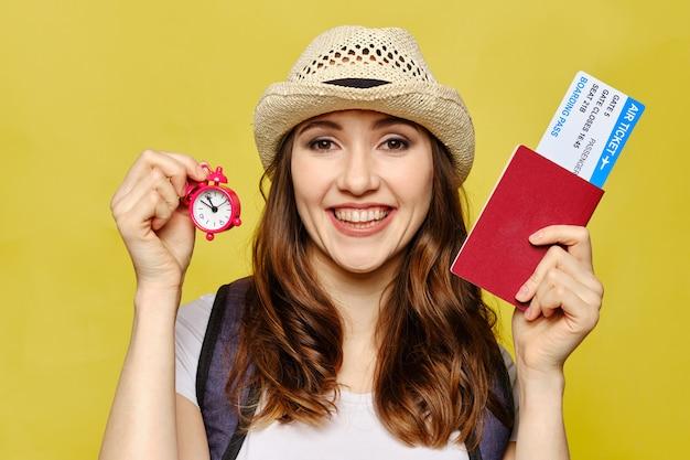 Garota detém um passaporte com bilhetes e um relógio em um fundo amarelo. Foto Premium