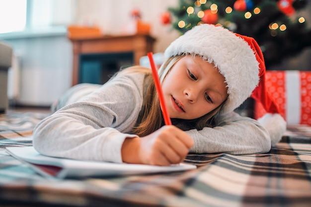 Garota diligente está deitado no blenket no chão e escrevendo a carta para o papai noel. ela usa lápis vermelho. garota é séria e concentrada. ela está no quarto sozinha. há uma árvore de natal com presentes atrás dela. Foto Premium