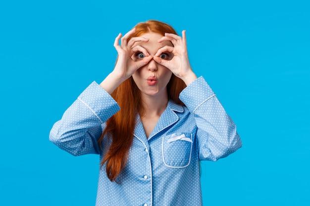 Garota dizendo uau olhando assustado vendo grande oportunidade para desconto de férias especiais. mulher ruiva atraente de pijama, olhando através dos dedos e dobrar os lábios divertido, parede azul Foto Premium
