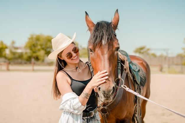 Garota do campo em um rancho com um cavalo castanho Foto Premium