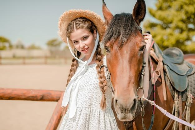 Garota do campo no chapéu de cowboy com um cavalo em uma fazenda Foto Premium