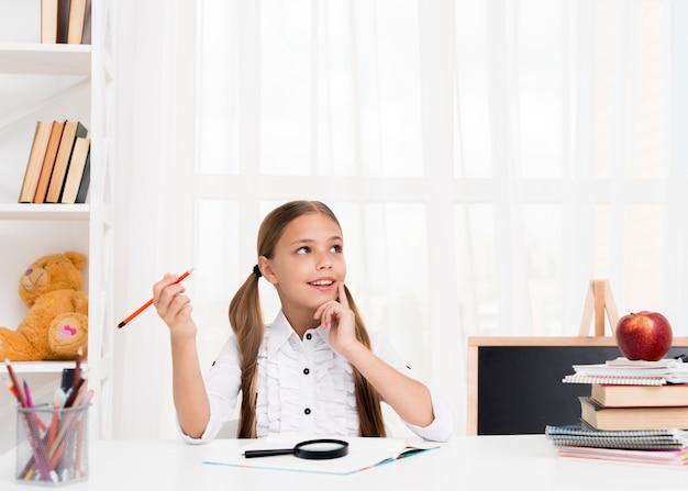 Garota do ensino fundamental pensando em resposta na tarefa Foto gratuita