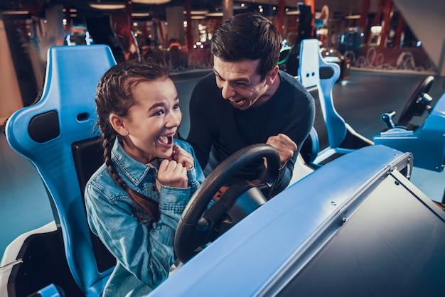 Garota é andar de carro no arcade. filha está ganhando. Foto Premium