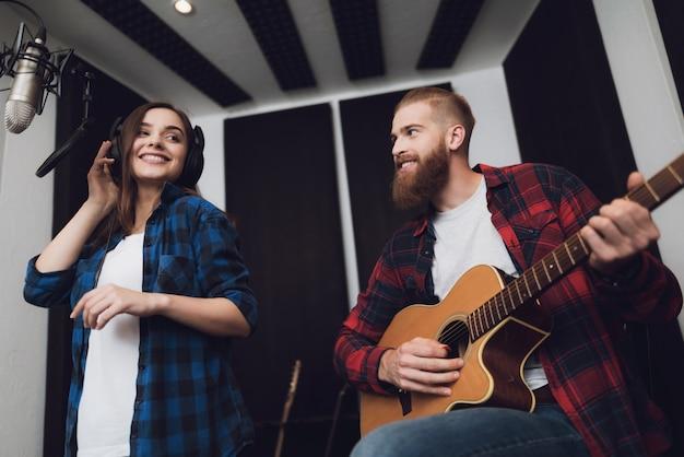 Garota e o cara cantam música para guitarra no estúdio de gravação moderno Foto Premium